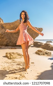 Portrait of latino woman with curly hair dancing at beach