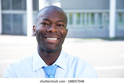 Portrait of a laughing african businessman in front of his office