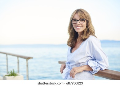 Portrait of a laughing attractive woman standing on the balcony at the sea.