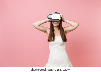 Portrait of laughing bride woman in white wedding dress, headset of virtual reality clinging to head isolated on pastel pink background. Organization of wedding concept. Copy space for advertisement