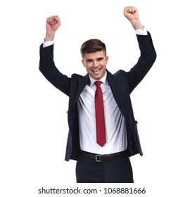 portrait of laughing businessman celebrating success with fists in the air while standing on white background and wearing a navy suit and a red tie