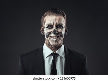 Portrait of laughing businessman with a make-up of the skeleton