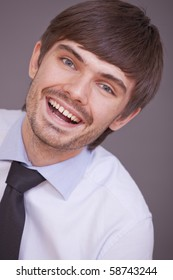 portrait of laughing businessman on grey background