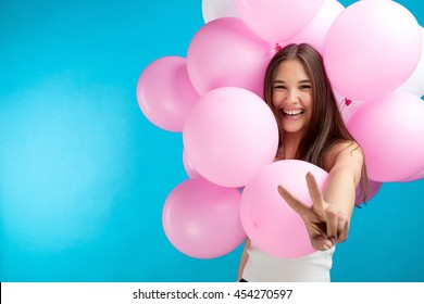 Portrait of laughing candid girl with pink air balloons with peace sign on blue background