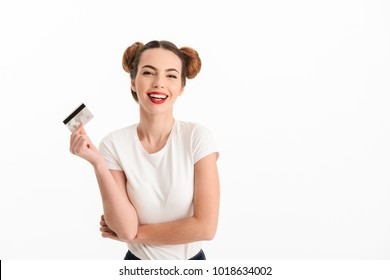 Portrait of a laughing casual girl showing credit card isolated over white background