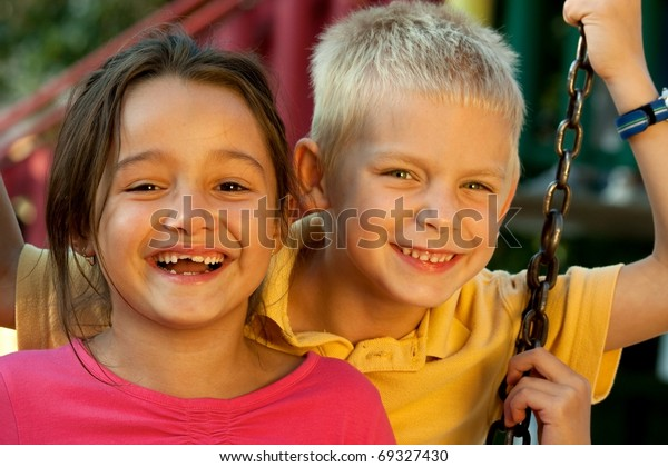Portrait of laughing children on swing playground outdoors