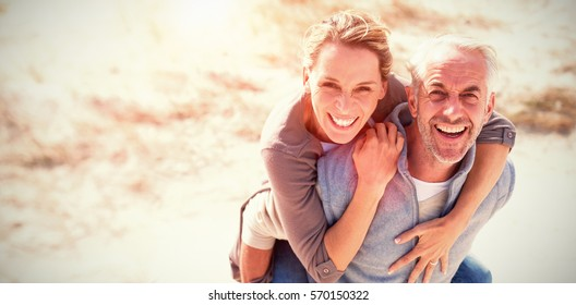 Portrait of laughing couple standing at beach on sunny day