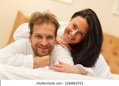 Portrait of laughing couple in white robes lying on bed, looking at camera and posing. Cheerful man and woman resting together and enjoying time spending in morning. Concept of happiness.