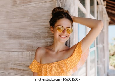 Portrait of laughing ecstatic lady with brown hair enjoying vacation at resort. Photo of inspired tanned woman expressing happiness while standing near wooden house.