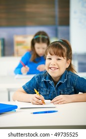 Portrait of laughing elementary age schoolgirl sitting in class looking at camera smiling, other girl in background.