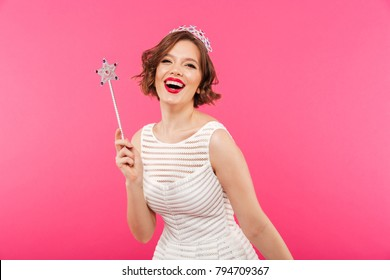Portrait of a laughing girl wearing crown and holding magic wand while looking at camera isolated over pink background
