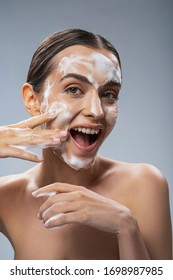 Portrait of laughing girl while she is washing face and standing in foam isolated on grey background stock photo