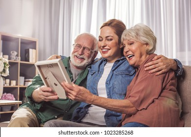 Portrait of laughing grandparents and smiling young woman looking at photo in room. Remembrance concept