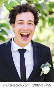 Portrait of a laughing groom with curly hair. He is wearing a black suit, in a buttonhole a buttonhole.