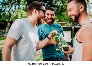 Portrait of laughing guys having a garden barbecue, grilling and cooking, having alcoholic beers