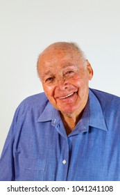 portrait of laughing happy elderly man in front of a white background