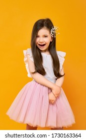 Portrait of laughing little child on bright yellow background