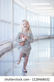Portrait of laughing little girl wearing striped dress dancing