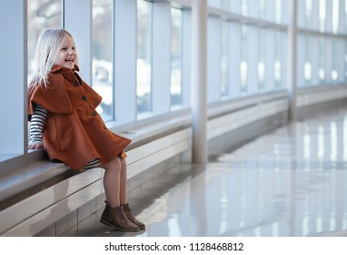 Portrait of laughing little girl wearing coat sitting in mall