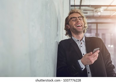 Portrait of laughing male holding phone in hand while leaning against wall inside. Copy space. Cheerful mind concept