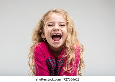 Portrait of laughing preteen girl with curly hair against plain background