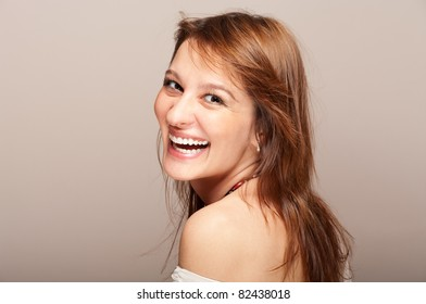 Portrait of laughing redhead woman turning around on gradient background