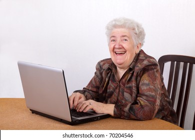 Portrait of laughing senior woman working at computer