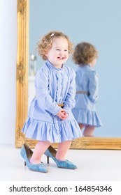 Portrait of a laughing toddler girl with beautiful curly hair wearing a blue dress is trying on her mother's elegant high heels shoes standing in front of a big mirror in a white bedroom