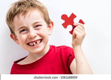 portrait of a laughing toothless boy finding a piece of jigsaw for concept of fun education, growing up difference or idea for child healthcare