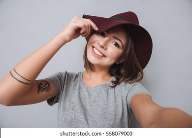 Portrait of a laughing woman in hat and scarf making selfie photo over gray background