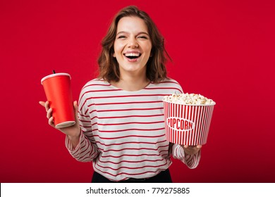 Portrait of a laughing woman holding popcorn and plastic cup isolated over pink background