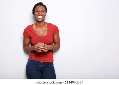 Portrait of laughing woman holding smart phone and standing by white wall