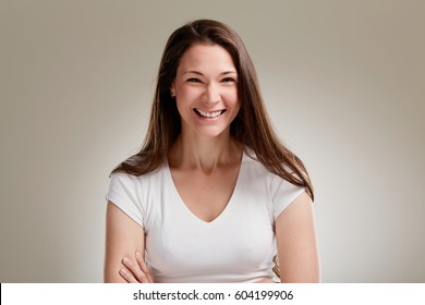 Portrait of laughing woman with long brunette hair on grey background.