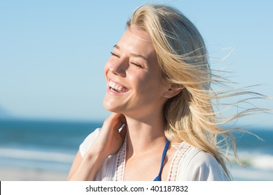 Portrait of laughing woman touching her hair. Cheerful attractive woman enjoying at beach. Joyous woman at sea shore laughing. Young blonde at sea shore with a toothy smile.
