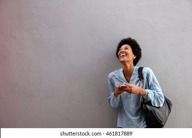 Portrait of laughing young african american woman with mobile phone standing against a gray wall