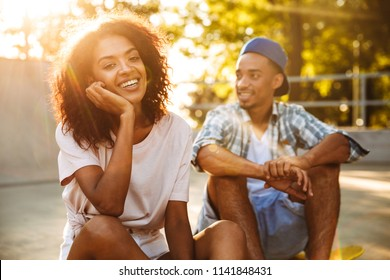 Portrait of a laughing young african couple with skateboard sitting together at the skate park