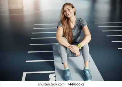 Portrait of laughing young female fitness trainer sitting in empty space after a long hard workout. Fitness concept.