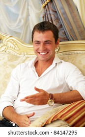 Portrait of a laughing young guy enjoying conversation with somebody