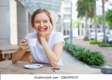 Portrait of laughing young lady drinking coffee at street cafe. Caucasian girl wearing white T-shirt resting at sidewalk cafe. Coffee break concept