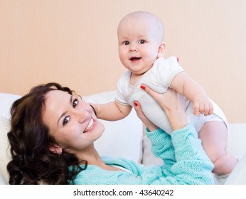 Portrait of laughing young mum together with a small son in a room interior