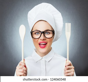 Portrait of laughing young woman cook chef holding wooden fork and spoon