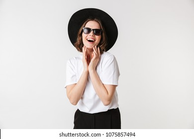 Portrait of a laughing young woman dressed in black hat and sunglasses posing while standing isolated over white background