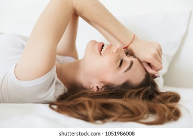 Portrait of a laughing young woman laying in bed at home