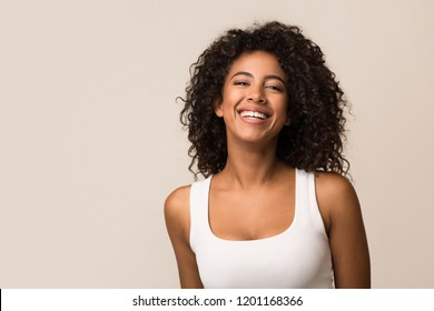 Portrait of laughing young woman standing against light background
