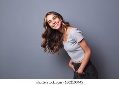 Porträt von lachender junger Frau, die gegen eine graue Wand steht.