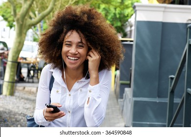 Portrait of laughing young woman walking with cellphone and earphones