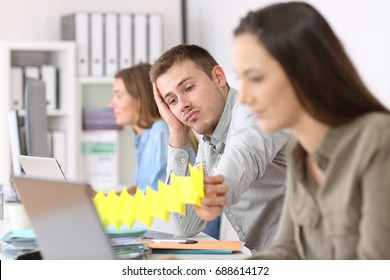 Portrait of a lazy employee boring sitting in a desktop between other workers at office