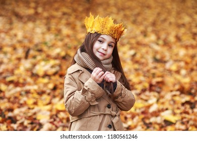Portrait liitle girl with crown of leaves in autumn park