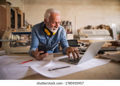 Portrait of a likeable old engineer holding cellphone and looking at the laptop