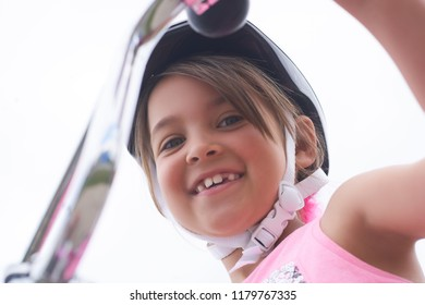 Portrait of a litte Cacasian girl in a pink safety helmet driving her bike.